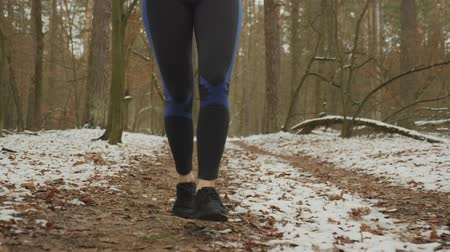 rajstopy : Close up of legs in tights and sneakers running outdoor. Female legs run in park. Woman feet jogging outdoor in forest at winter. Girl in blue tights runs and doing daily workout exercises Wideo