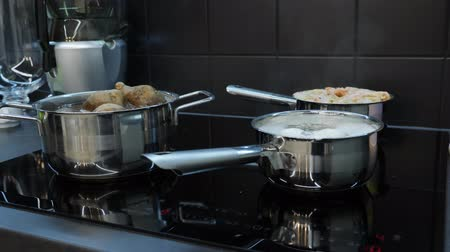 induction cooker : Food cooking process on induction electric stove. Process of cooking eggs, shrimps and potatoes. Vegetables are cooked in big pans on stove