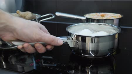 induction cooker : Chef takes off cooked eggs from electric stove. Home cooking. Vegetables are cooked in pans on induction electric stove. Process of preparing healthy food. Smart kitchen Stock Footage