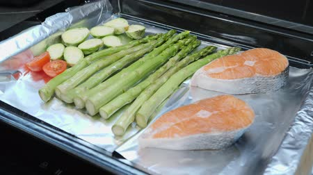 seafood recipe : Process of cooking vegetables in oven. Fresh tomatoes, Brussels sprouts and green asparagus on oven tray. Healthy food eating. Chef cooks salmon steak at restaurant kitchen