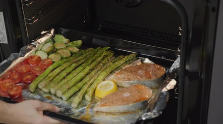 гарнир : Hands put oven tray with red fish salmon and vegetables in the electric oven and closes door. Cooking Concept