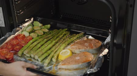 гарнир : Chef starts grilling salmon seasoned with tomatoes, Brussels sprouts and green asparagus in the oven. Slow motion.