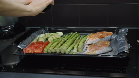 гарнир : Hands seasoning vegetables and salmon with spices and salt. Cooking Concept