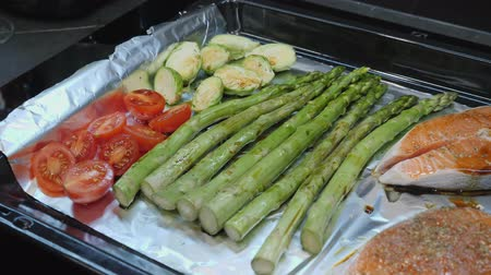 asperges : Brussels sprouts and green asparagus with tomatoes and trout salmon being seasoned with pepper and spices.