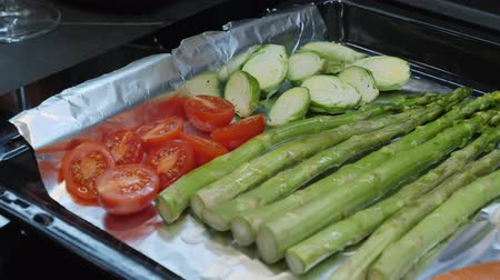 körítés : Hands seasoning fresh vegetables on oven tray with olive oil before grill Stock mozgókép