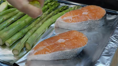 гарнир : Hands pouring olive oil on red salmon slices before cooking in the oven.