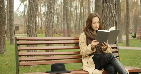 kniha : Young cute girl sitting in park on a bench and reading a book with black hat placed near her. Reading concept