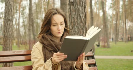 roman : Attractive woman opens a book and turning white pages then starts to read a novel while sitting in autumn cold park alone wearing brown scarf