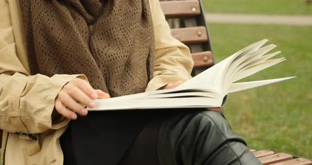 yaprak döken : Woman hands opening book and turning pages while reading. Book reading concept. Female with brown scarf reading a book in park.