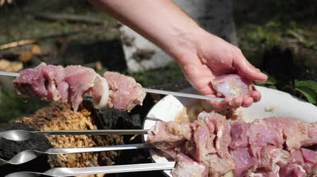 appetizing shish kebab : Man chef sticks meat on skewer. Meat in onion marinade. Outdoor barbecue. Cooking meat on grill