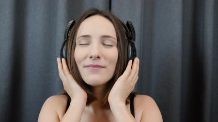 шнур : Woman listens to music in headphones. Shy sensual female puts on headphones on camera, extra close up view. Face of sexy brunette. Young girl taking off headphones. Smiling woman stops listen to music