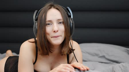 sensuous : Woman enjoying music in headphones while lying on bed. Sexual shy female listening to music with closed eyes and sending air kiss. Adult sensuous girl in black lingerie lies on bed and listens to music