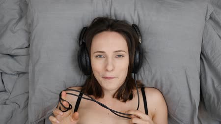 kordon : Sensual shy female listens to music in headphones. Young sexual woman lies on bed and flirts to camera, top view. Portrait of girl lying on bed and listening to music. Female is flirting and embarrassed