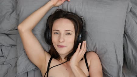 sensuous : Girl in headphones listening to music in bed. Young sensuous woman lying on bed and taking off headphones. Top view of female lies on bed and bites lips, portrait footage. Smiling woman listens to music