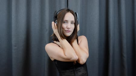sensuous : Woman in lingerie listens to music from headphones. Sensuous shy female in big headphones and black underwear listening to music and dancing. Slow motion