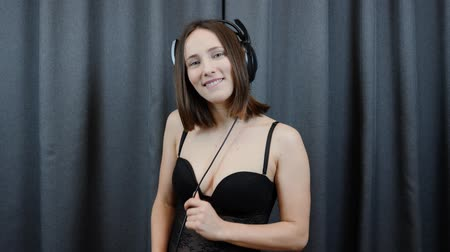 playlist : Sexy brunette playing with headphones wire. Woman in big headphones and black underwear flirting and seducing to camera. Female listens to music against gray background. Slow motion