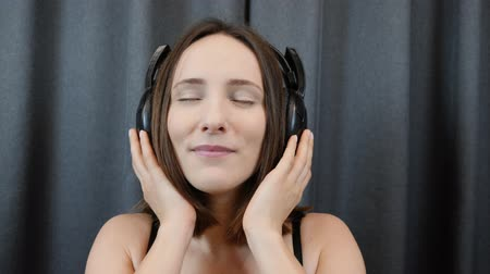 shy girl : Woman listens to music in headphones. Shy sensual female puts on headphones on camera, extra close up view. Face of sexy brunette. Young girl taking off headphones. Slow motion