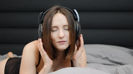 shy girl : Sexy brunette in headphones lying on bed. Sensual shy female in black lingerie listens to music in bed. Portrait of charming girl. Attractive caucasian woman takes off headphones. Slow motion Stock Footage