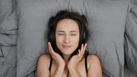 acustica : Top view of woman in big headphones lying on bed. Female in underwear listens to music and smiles to camera. Caucasian good-looking girl in lingerie lies on bed and listening song. Slow motion