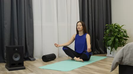 balanceamento : Relaxed young woman in classic blue sports clothing is meditating in lotus position sitting on yoga mat with closed eyes at home. Female sitting on the floor and posing lotus finger gesture Stock Footage