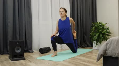 kiegyensúlyozó : Female stretches hamstring muscles, leg muscles with pigeon pose. Young fit sporty brunette in blue top, black leggings does fitness exercises on mat in bright room. Woman stretching hip.