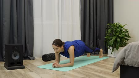 břišní : Girl does plank pose on yoga mat. Young fit female athlete doing plank as part of her daily exercises. Woman in blue clothes stands in plank position. Attractive brunette doing yoga poses