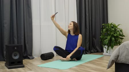 kiegyensúlyozó : Female doing selfie on yoga mat at home. Young caucasian woman sitting in zen position on floor and meditating. Carefree adult girl doing photos on phone before yoga practicing. Slow motion