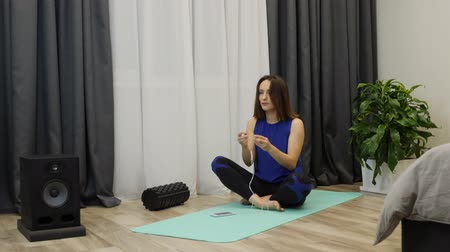 balanceamento : Woman puts on earphones and preparing for yoga practicing. Caucasian young female in blue sportswear sitting on yoga mat and putting on earphones before meditation. Slow motion