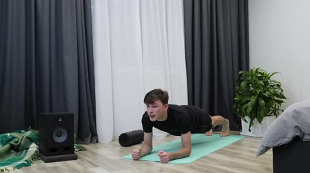 břišní : Male athlete does plank pose on mat. Young fit man doing plank as part of his daily exercises. Fitness trainer in black clothes stands in plank position. Workouts concept