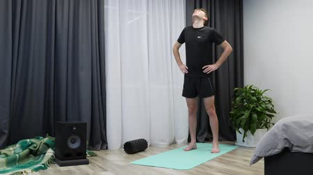 energický : Male does physical exercise at home. Athletic fit boy doing fitness and aerobic exercises on yoga mat. Young male athlete with trained body warms up before indoor workout. Healthy lifestyle concept