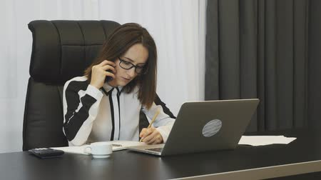 analista : Businesswoman working in modern office. Confident female writing notes while talking on phone. Thoughtful concerned woman negotiates by phone at her office. Employee works on laptop. Business concept