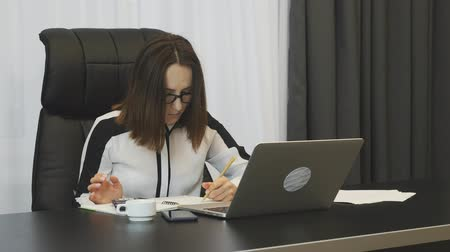 conserva : Woman is considering company expenses in office. Businesswoman keeps accounts at work. Confident concentrated female works in office. Brunette lady doing job. Business concept Stock Footage