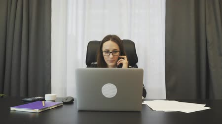 secretário : Businesswoman talking on phone in her office. Female consultant talks to company partners on smartphone. Young confident woman makes deal with financial partners by phone. Business success concept