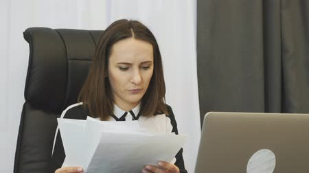analista : Shocked female boss looking at financial report. Worried businesswoman looks at company accounts. Upset woman watching at reports and worries about situation on financial stock market Archivo de Video