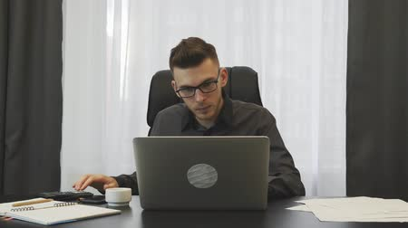 conserva : Broker working in office. Young successful businessman works on laptop in office. Man taking notes in notebook sitting at his office desk. Financier keeps accounts of company. Business success concept Stock Footage