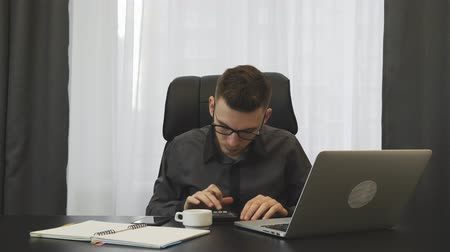 conserva : Businessman keeps accounts in modern office with laptop. Young male accountant checking financial report. Young man makes report using calculator and notebook. Broker working at workplace in office