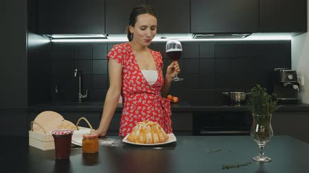 kırmızı şarap : Woman drinks wine at home modern kitchen. Young beautiful female prepared homemade pie and drinking red wine. Portrait of housewife in professional kitchen. Healthy lifestyle and food concept Stok Video