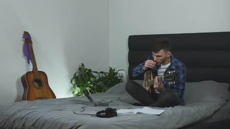 вести : Man creating new song on electric guitar. Musician is taking notes and practicing guitar lessons. Young millennial is learning guitar solo sitting on bed at living room. Music concept