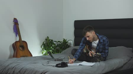skladatel : Male practicing guitar. Young caucasian man in blue t-shirt is learning on electric guitar on bed at modern home. Musician creating new song at home. Attractive guy playing on guitar