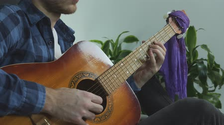 string instrument : Bearded young musician playing lead guitar solo on acoustic guitar sitting on bed at home practicing for live concert. Stock Footage