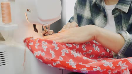 pano : Details of sewing machine. Close up of womans hands working on overlock. Female designer sew on sewing machine. Fashion and creation concept Stock Footage