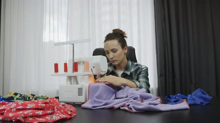 шить : Professional seamstress is sewing fabric at tailors studio. Portrait of young woman designer creating and working on hand made dress. Female tailor sews on sewing machine Стоковые видеозаписи