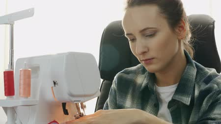 ruhakészítés : Close up of professional woman tailor sews on sewing machine. Portrait of young beautiful seamstress working and creating hand made dress in tailors studio. Creation and tailoring clothes