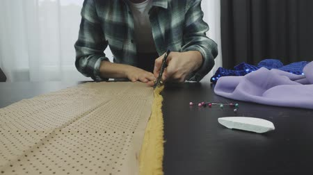 шитье дамского платья : Woman cutting fabric with scissors in tailors studio, soap slice, safety pins lying on table. Close up of scissors cuts fabric. Creation and tailoring clothes. Fashion concept