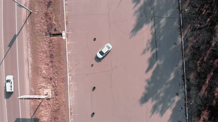 no traffic : Driver practicing to drive car at abandoned parking lot, aerial drone top view. Car is in abandoned parking lot