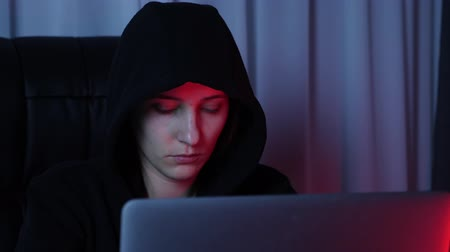 włamywacz : Female face looking at laptop screen. Close up of hacker face looking on computer screen and typing on keyboard and coding script. Woman in black hoodie breaks password and online security protection