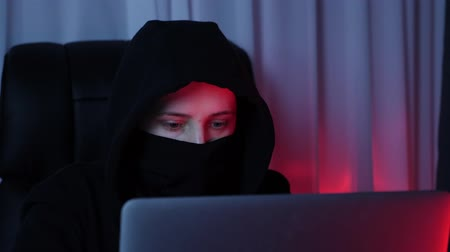 włamywacz : Woman face in black mask and hoodie looking at computer screen and breaking password. Young hacker breaks security protection on laptop screen. Concept of social security, online, virus protection Wideo
