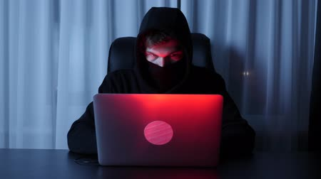 włamywacz : Man hacker face looking at computer screen. Male in black mask and hood breaking password and online social security protection. Hacker programming scripts on laptop. Security and viral concept