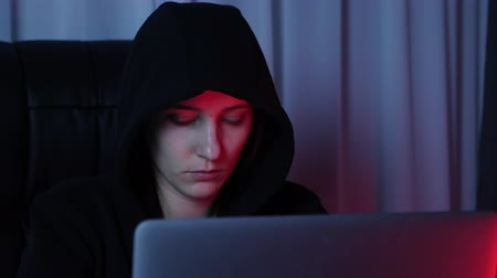 włamywacz : Female face looking at laptop screen. Close up of hacker face looking on computer screen and typing on keyboard. Woman in black hoodie breaks password and security protection. Slow motion Wideo