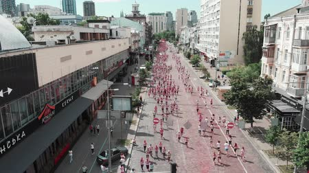 résztvevő : Kyiv  Ukraine - June 2, 2019 - People taking part in run competition Color Run Kyiv. Drone flying above street with women and men running among city center. Happy participants at run race, drone view Stock mozgókép